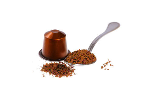 Spoonful of instant coffee granules and capsule, isolated over white background